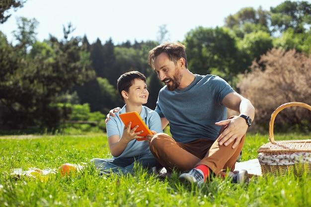 Popatrz tutaj. ładny inspirowany chłopiec trzymający tablet, siedząc z ojcem w parku