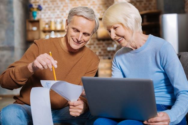 Popatrz tutaj. miły radosny starszy mężczyzna trzymający swoje notatki i wskazujący na nie, pokazując je przyjemnej starszej kobiecie