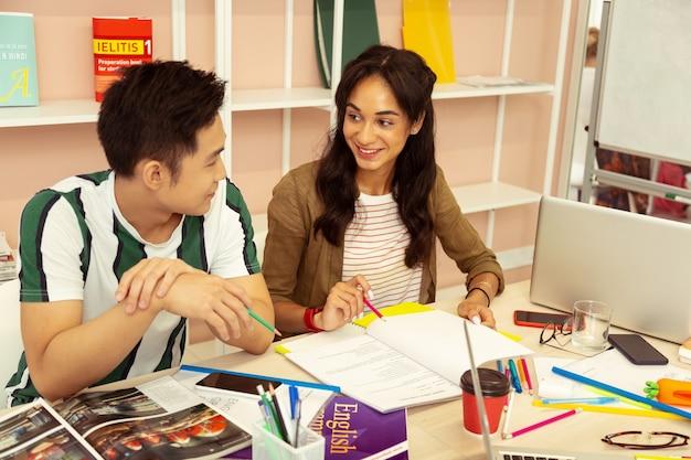 Popatrz tutaj. zachwycony azjata opierając się łokciami na stole, słuchając swojego kolegi z klasy