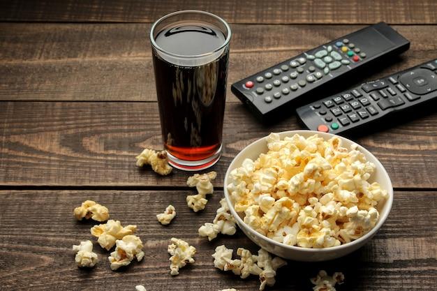 Popcorn, coca cola i pilot do telewizora na brązowym drewnianym stole, koncepcja oglądania filmów w domu.