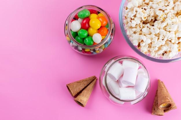 Popcorn i pianki marshmallows z widokiem z góry wraz z kolorowymi cukierkami na różowym, kolorowym cukrze lizakowym