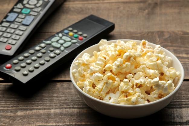 Popcorn i pilot do telewizora na brązowym drewnianym stole, koncepcja oglądania filmów w domu.