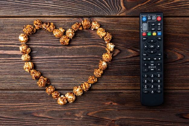 Popcorn i pilot do telewizora na ciemnym tle drewnianych.