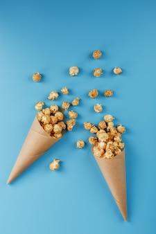 Popcorn karmelowy w papierowej kopercie na niebieskim tle. pyszna pochwała za oglądanie filmów, seriali, kreskówek. wolna przestrzeń, zbliżenie. minimalistyczna koncepcja.