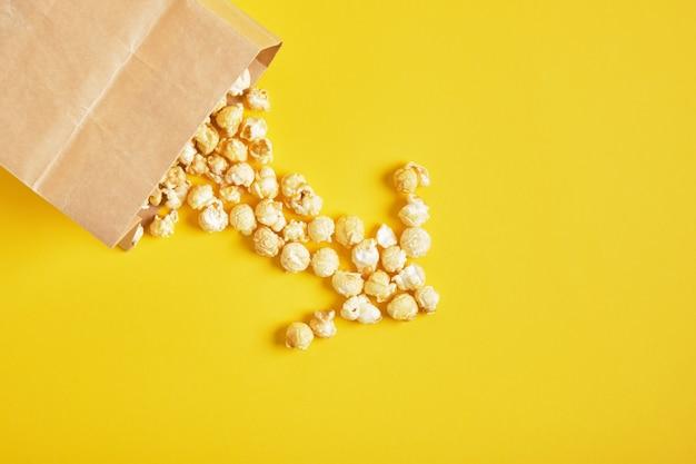 Popcorn karmelowy w papierowej torbie na żółtym tle
