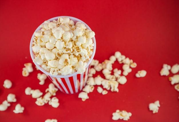 Popcorn maślany w czerwonej filiżance popcornu, przekąska w domu lub w kinie