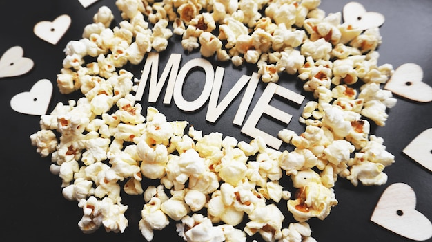 Popcorn na czarnym tle. oglądanie filmu z popcornem. skopiuj miejsce. pop kukurydza. widok z góry. leżał płasko. film z drewnianymi literami z sercami