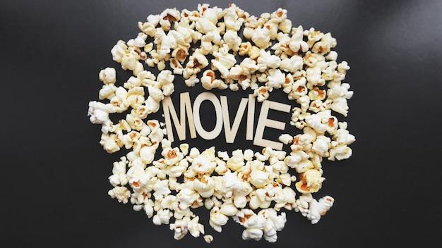 Popcorn na czarnym tle. oglądanie filmu z popcornem. skopiuj miejsce. pop kukurydza. widok z góry. leżał płasko. film z drewnianymi literami