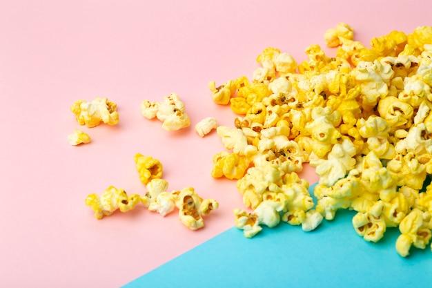 Popcorn na kolorowym tle. minimalna koncepcja żywności. rozrywka, film i treści wideo. estetyka z lat 80. i 90