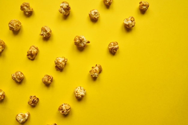 Popcorn na żółtym tle. stylizm minimalizmu. otwarta kompozycja