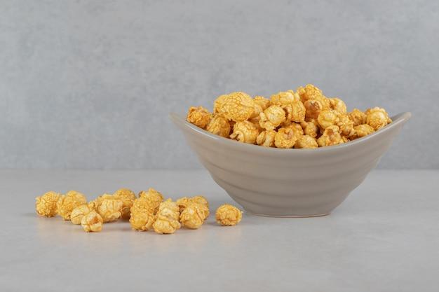 Popcorn oblany karmelem w środku i obok małej miseczki na marmurowym stole.