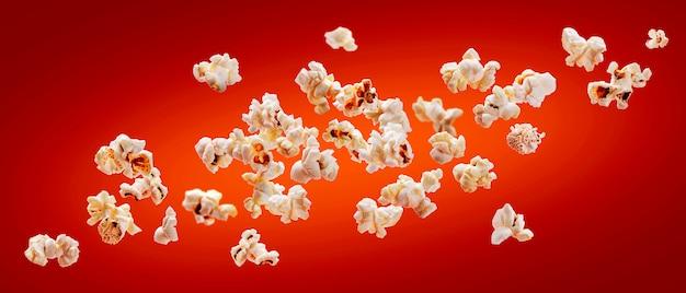 Popcorn odizolowywający na czerwonym tle. popcorn spadający lub latający.