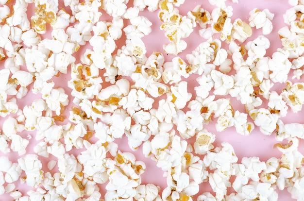 Popcorn rozrzucony na różowym pastelu