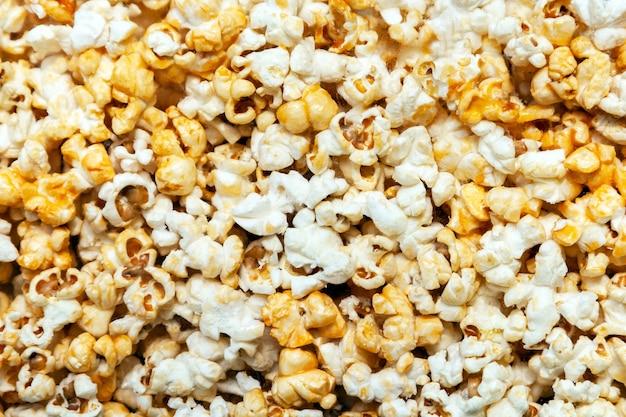 Popcorn tekstura tło. sterta popcornu za szybą