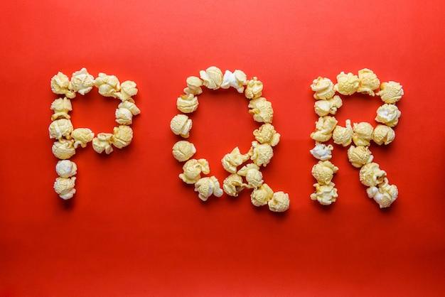 Popcorn tworząc literę p, q, r na czerwonym tle