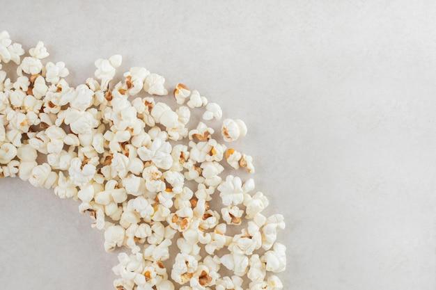 Popcorn ułożony w łuk na marmurowym stole.