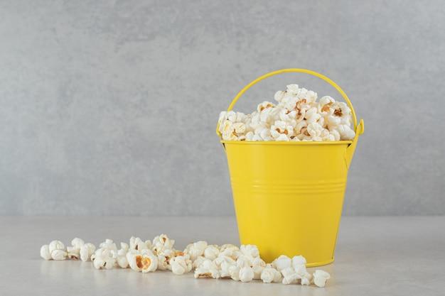 Popcorn upchnięty do małego wiaderka i rozsypany na marmurze.