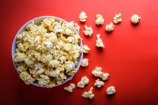 Popcorn w białym bowl na czerwonym tle, selektywne fokus na popcorn w białym bowl