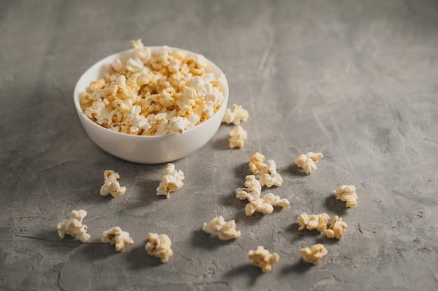 Popcorn w białym talerzu na betonowym szarym tle