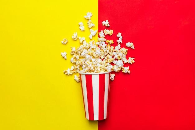 Popcorn w czerwono-białym kartonie na czerwonym i żółtym