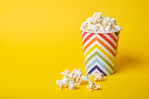 Popcorn w jasny świąteczny kubek papierowy na żółtym tle