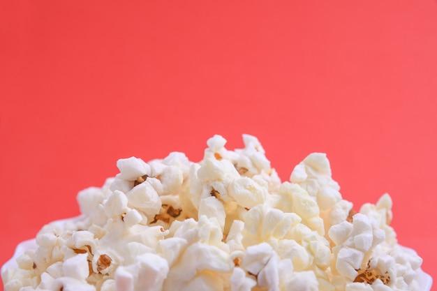 Popcorn w misce na czerwonym tle. ścieśniać. widok z góry.