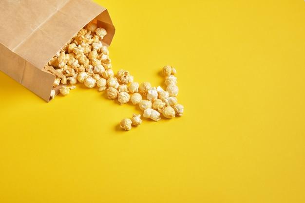 Popcorn w opakowaniu papierowym na żółtym tle kopii przestrzeni