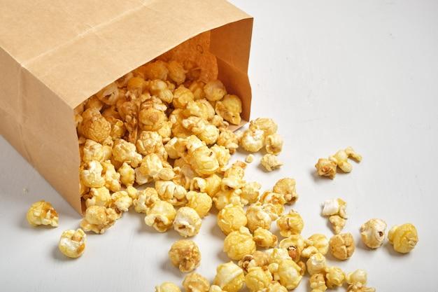 Popcorn w papierowej torbie na szarym tle