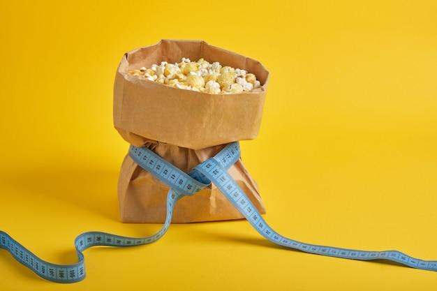 Popcorn w papierowej torbie z niebieską miarką na żółtym tle