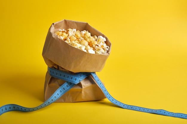 Popcorn w papierowej torbie z niebieską taśmą mierniczą na żółtym tle kopii przestrzeni