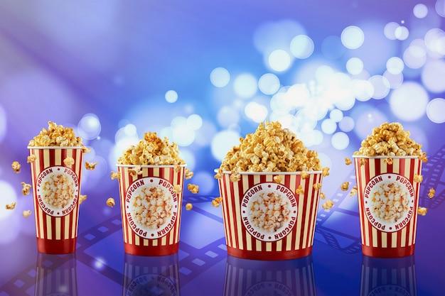 Popcorn w papierowych kubkach na niebieskim tle