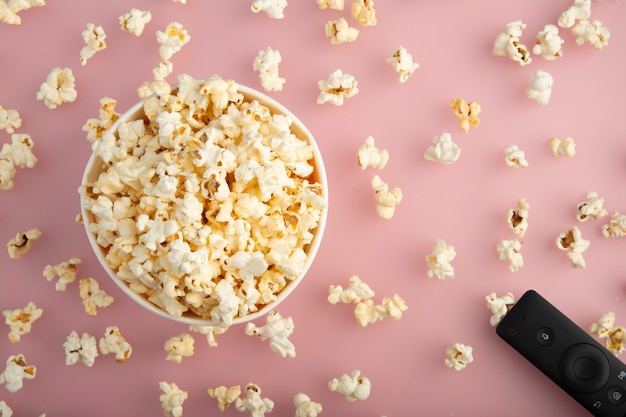 Popcorn w papierowym pudełku lub paski kubek papierowy oglądany z góry na białym tle na różowo