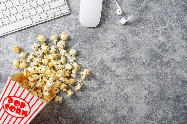 Popcorn w pasiastych wiadrach i klawiaturze komputera na szarym tle cementu obraz koncepcji kina