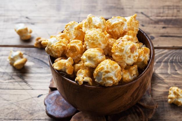 Popcorn w polewie karmelowej w drewnianych talerzach na rustykalnym stole.
