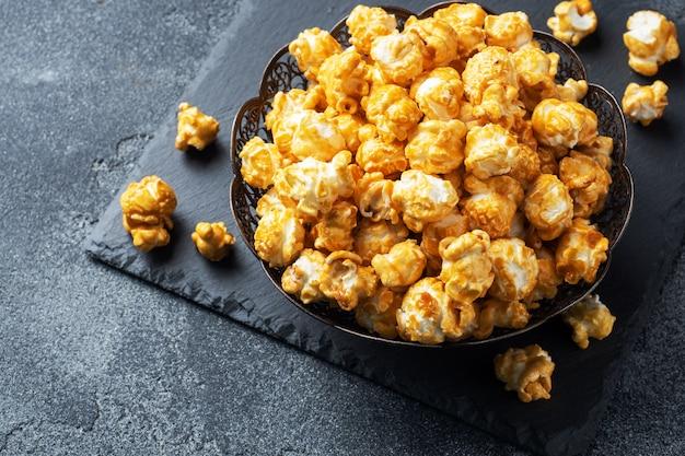 Popcorn w polewie karmelowej w talerzu na ciemnym betonowym stole.