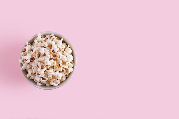 Popcorn w talerzu na różowym tle