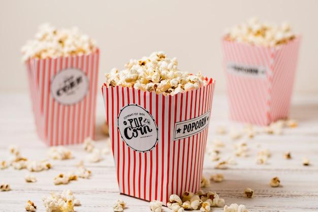 Popcorn w trzy czerwone i białe pudełko popcornu na drewnianym stole