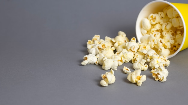 Popcorn w żółtym papierowym kubku na szarym tle. skopiuj miejsce