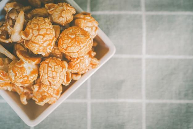 Popcorn wielkoziarnisty zmieszany z migdałami, różne orzechy w misce, bardzo apetyczny. umieszczony na pasiastym welonie, obraz w widoku z góry