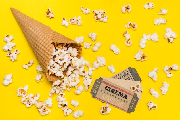 Popcorn wylewający się z rożka waflowego z biletami do kina na żółtym tle