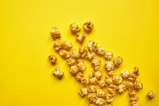 Popcorn z karmelem na jasnym żółtym tle