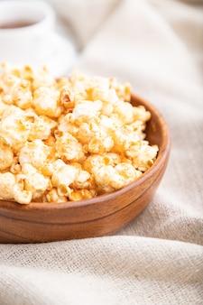 Popcorn z karmelem w drewnianej misce i filiżankę kawy na białym tle drewniane i lnianą tkaniną. widok z boku, bliska, selektywna ostrość.