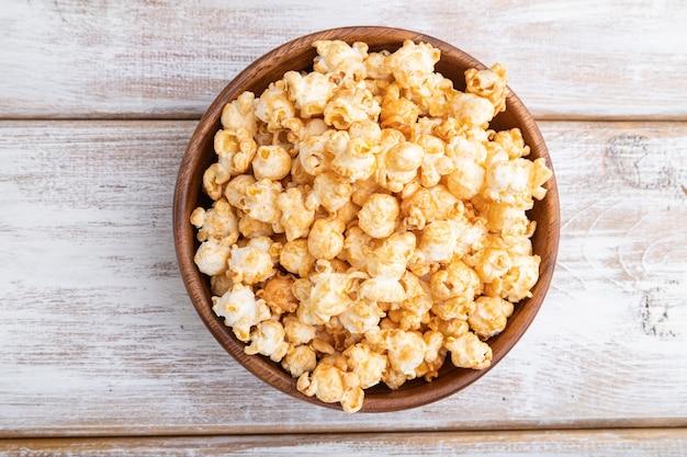 Popcorn z karmelem w drewnianej misce na białym tle drewnianych. widok z góry, płaski układ, z bliska.