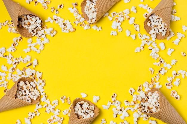 Popcorns z gofrów rożkami na żółtym tle z przestrzenią dla pisać tekscie