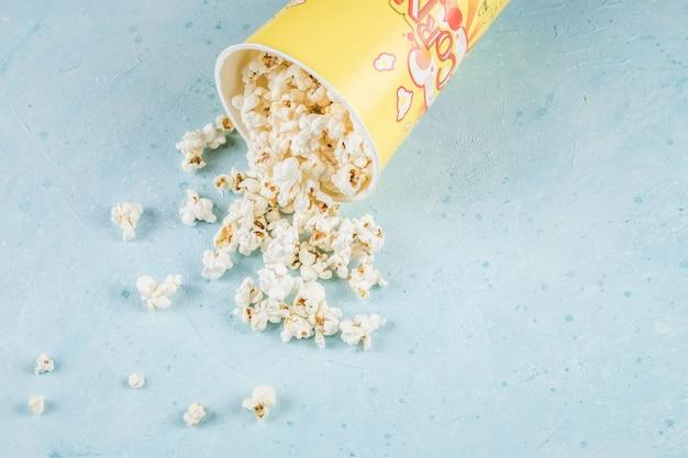 Popcorny z żółtego pojemnika na niebieskim stole