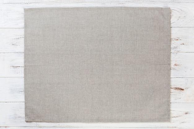 Popielata sukienna pielucha na białej nieociosanej drewnianej powierzchni