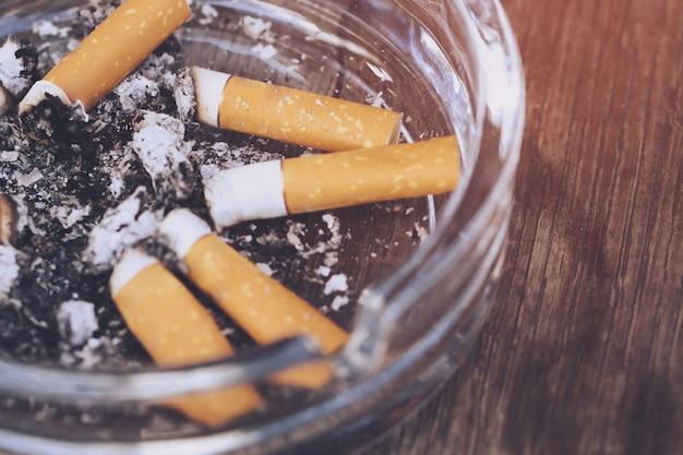 Popielniczka pełna niedopałków papierosów z bliska na tle drewna