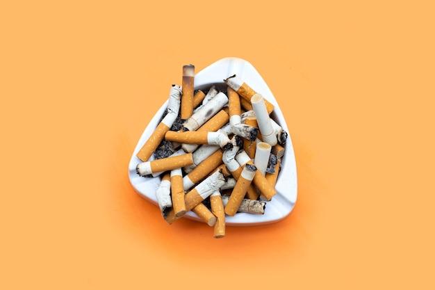 Popielniczka z papierosami na pomarańczowym stole.