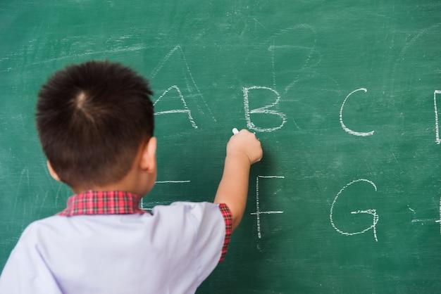 Popiera azjatycki małe dziecko chłopiec dzieciniec pisze abc z kredą na zielonym blackboard w ucznia mundurze