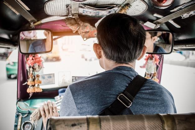 Popiera azjatycki mężczyzna jeżdżenia silnika trójkołowiec lub tuk tukon droga w mieście bangkok, tajlandia